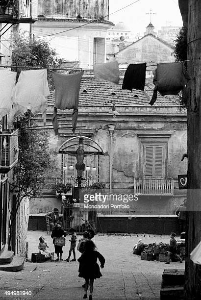 A sloping alley of the Old Town with a scene of daily life in a popular neighborhood some wooden boxes full of fruits and vegetables are put for sale...