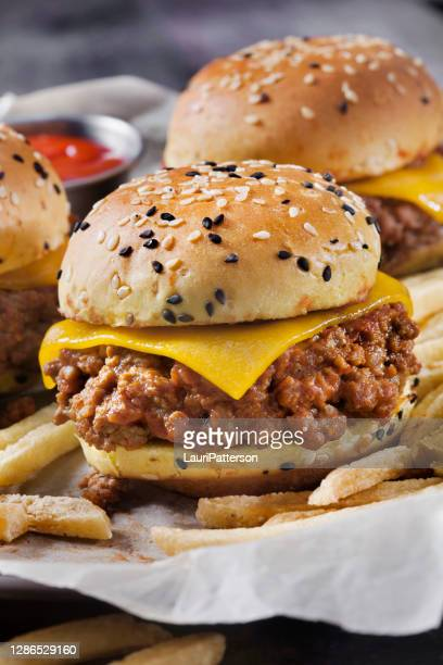 sloppy joe sliders with cheddar cheese on a brioche sesame seed bun with fries - sloppy joe, jr stock pictures, royalty-free photos & images
