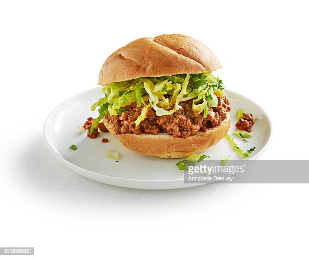 sloppy joe with lettuce on white plate on white - sloppy joe, jr stock pictures, royalty-free photos & images