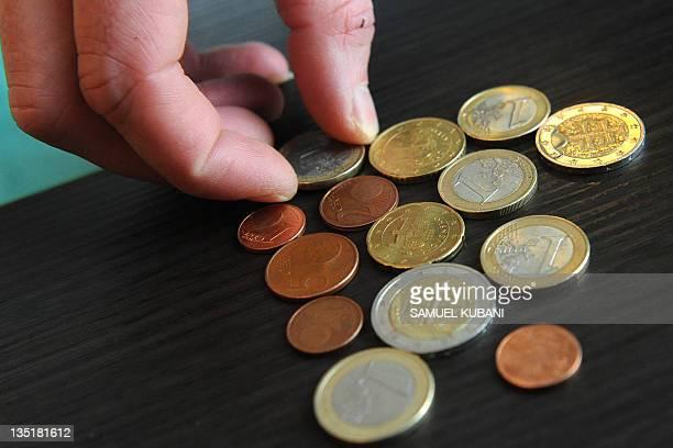 A Slovak counts euro coins in Bratislava on December 7 2011 AFP PHOTO / SAMUEL KUBANI
