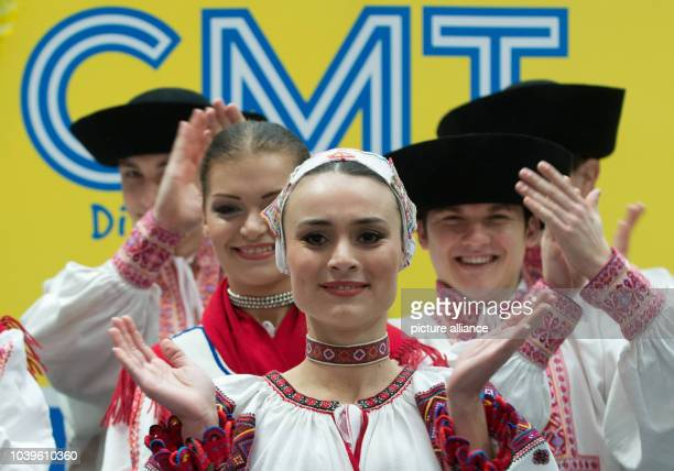Slovak dancers of the folk ensemble Lucnica peform in front of the logo of the tourism fair CMT in Stuttgart Germany 11 January 2013 The CMT tourism...