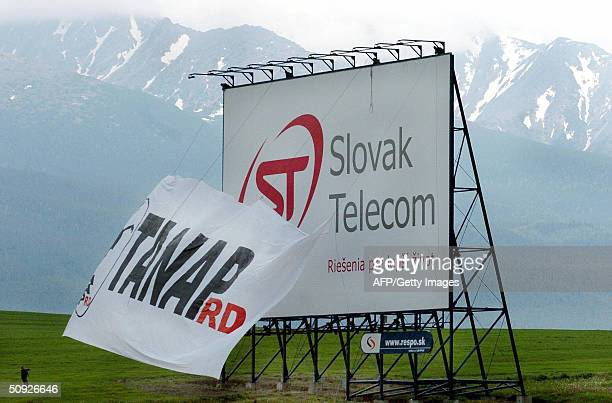 Slovak enviromental activists from the group Wolf hoist a banner to cover a controversial Slovak Telecom advertising billboard installed apparently...