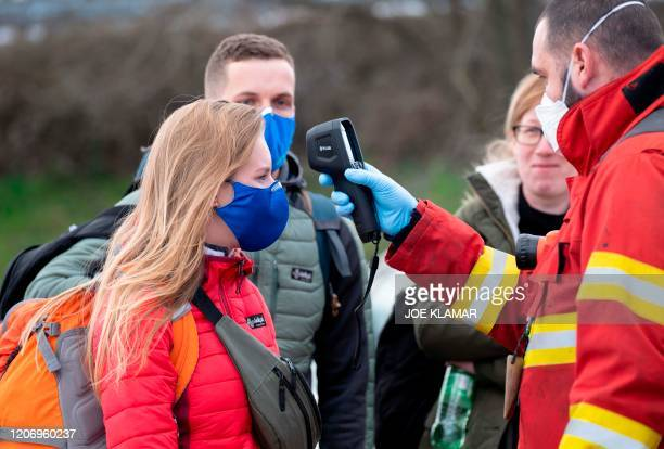 Slovak firefighter checks the temperature of a woman wearing a protective facemask due to the coronavirus COVID-19 crossing the Bratislava-Jarovce...