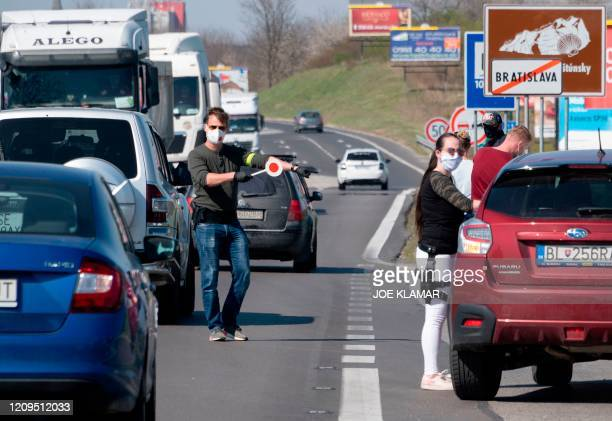 Slovak police officers stop cars to check the purpose of their travel between Bratislava and Malacky counties near the village of Zahorska Bystrica,...
