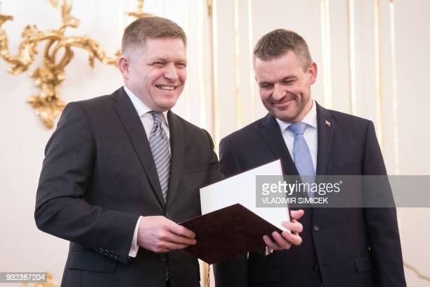 Slovak Prime Minister Robert Fico share a laugh with deputy premier Peter Pellegrini as he waits for his audience to hand in his letter of...