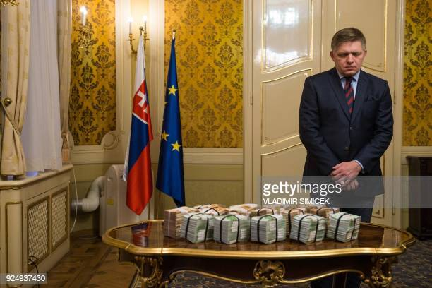 Slovak Prime Minister Robert Fico stands behind bundles of Euro banknotes during a press conference on the murder case of a leading journalist who...