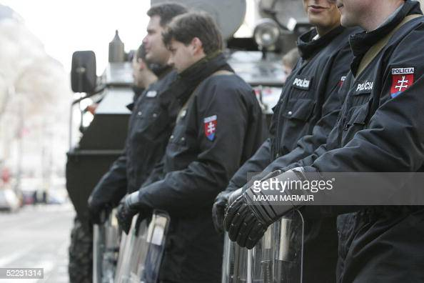 Slovak riot police officers stand guard in front of APC in