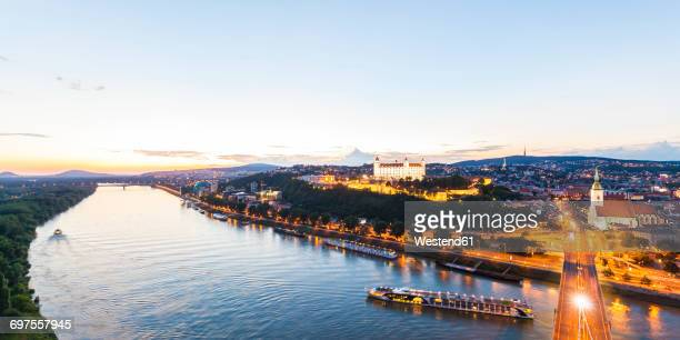 slovakia, bratislava, cityscape with river cruise ships on the danube at evening twilight - bratislava stock pictures, royalty-free photos & images