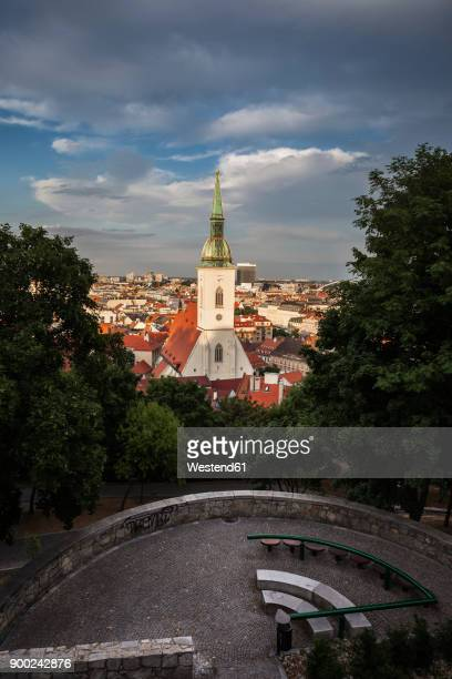 Slovakia, Bratislava, cityscape with St. Martins Cathedral at sunset, hill park terrace with benches