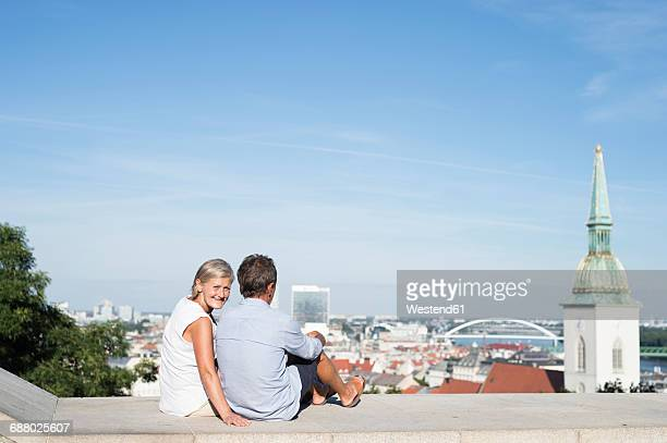 Slovakia, Bratislava, couple sitting on a wall looking at view