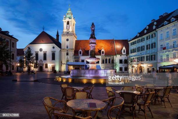 Slovakia, Bratislava, Old Town, Main Square at night with cafe restaurant tables, Roland Fountain and Town Hall