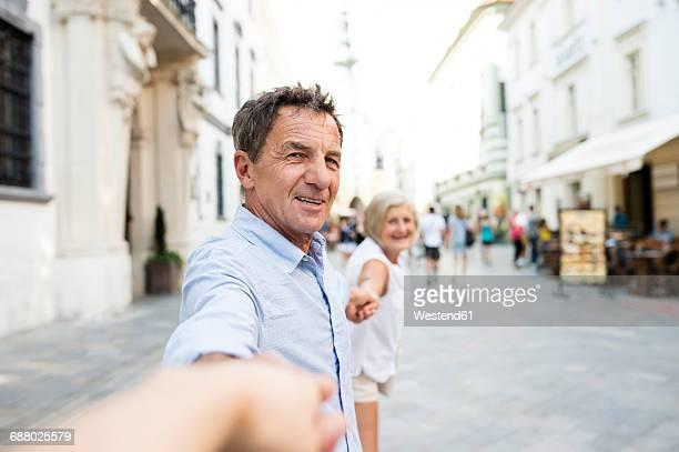 Slovakia, Bratislava, portrait of happy senior holding hands on the street