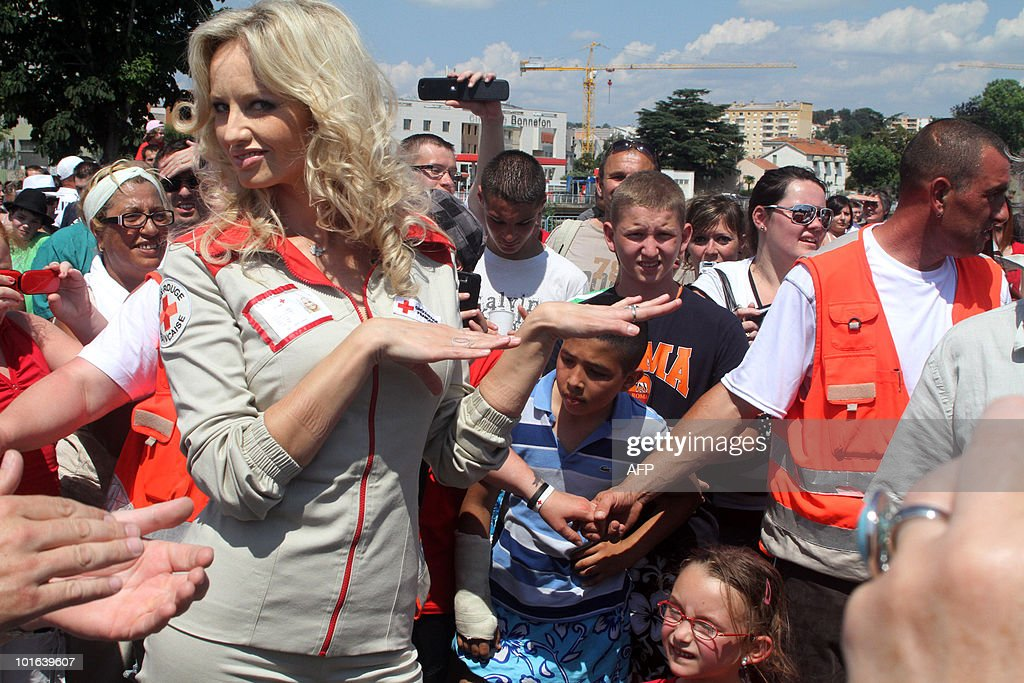 Slovakian born French goodwill ambassador and top-model Adriana Karembeu (L) takes part in a 'flash mob' as part of the launch of the Red Cross 2010 national fundraising campaign by French Red Cross (Croix Rouge française) on June 5, 2010 in Ales, southern France. A flash mob (for flash mobilisation) is a large group of people who assemble suddenly in a public place, and perform an unusual act for a brief time.