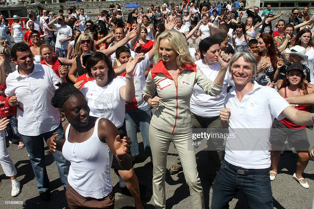 Slovakian born French goodwill ambassador and top-model Adriana Karembeu (C) takes part in a 'flash mob' as part of the launch of the Red Cross 2010 national fundraising campaign by French Red Cross (Croix Rouge française) on June 5, 2010 in Nimes, southern France. A flash mob (for flash mobilisation) is a large group of people who assemble suddenly in a public place, and perform an unusual act for a brief time.