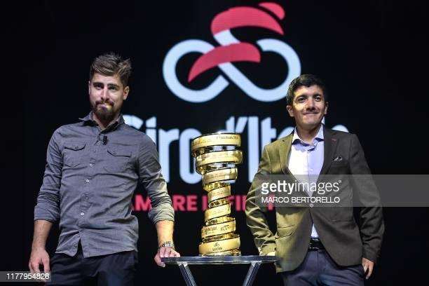 "Slovakian cyclist Peter Sagan and winner of the 2019 Giro d'Italia cycling race, Ecuadorian cyclist Richard Carapaz pose with the winner's ""Never..."