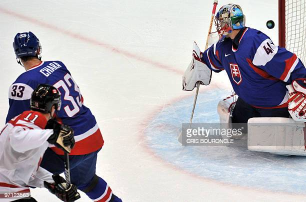 Slovakian goalkeeper Jaroslav Halak misses the puck by Canadian forward Patrick Marleau giving Canada their first goal during the Men's Semifinals...