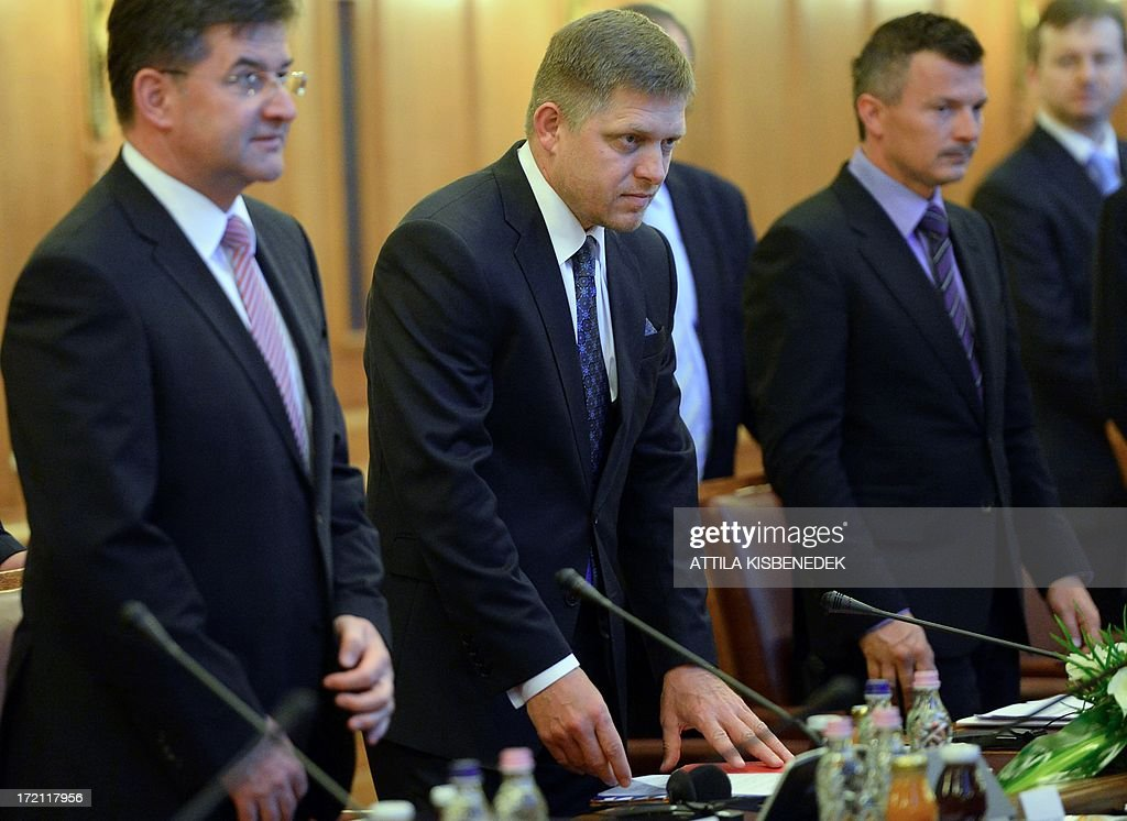 Slovakian Prime Minister Robert Fico (2ndR), Foreign Minister Miroslav Lajcak (L) and Transport, Construction and Regional Development Minister Jan Pociatek (R) arrive for a plenary meeting with the Hungarian government at the Hunter Hall of the parliament building in central Budapest on July 2, 2013. Fico met today with Hungarian Prime Minister Viktor Orban during his one-day working visit.