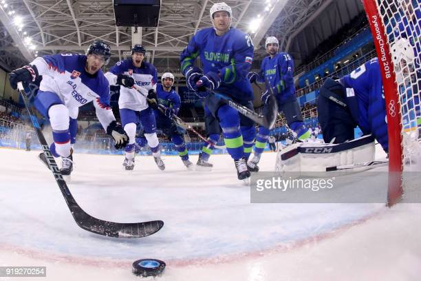 Slovakia's Andrej Kudrna and Michal Cajkovsky react as the puck slides into the net for a goal in the men's preliminary round ice hockey match...