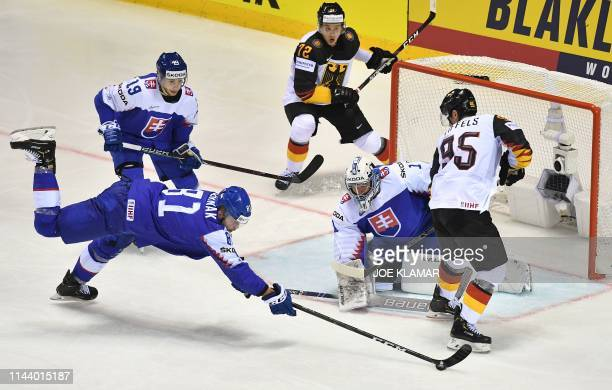 Slovakia's defender Erik Cernak stops the puck in front of Slovakia's goalkeeper Marek Ciliak during the IIHF Men's Ice Hockey World Championships...