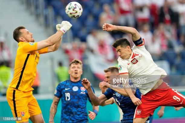 Slovakia's goalkeeper Martin Dubravka deflects the ball next to Poland's forward Robert Lewandowski during the UEFA EURO 2020 Group E football match...