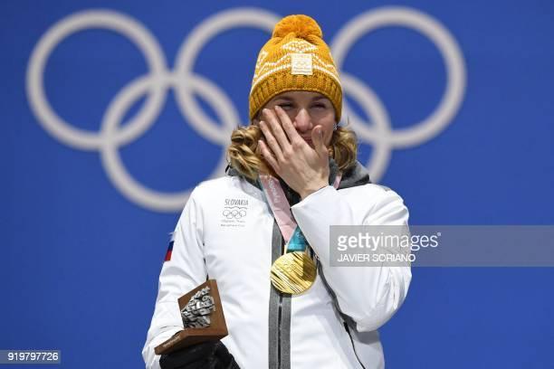 Slovakia's gold medallist Anastasiya Kuzmina wipes her tears on the podium during the medal ceremony for the biathlon women's 12,5km mass start at...