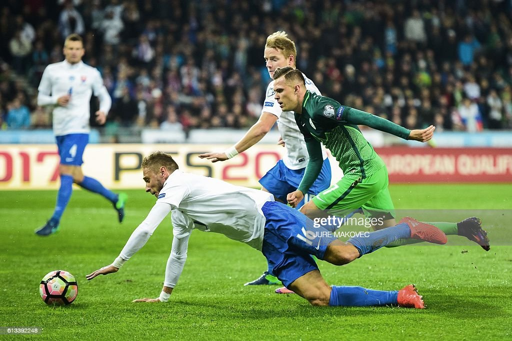 Slovakia's Kornel Salata (L) vies for the ball with Slovenia's Josip Ilicic (R) during the FIFA World Cup qualifying football match between Slovenia and Slovakia at Stozice Stadium in Ljubljana on October 8, 2016. / AFP / Jure MAKOVEC
