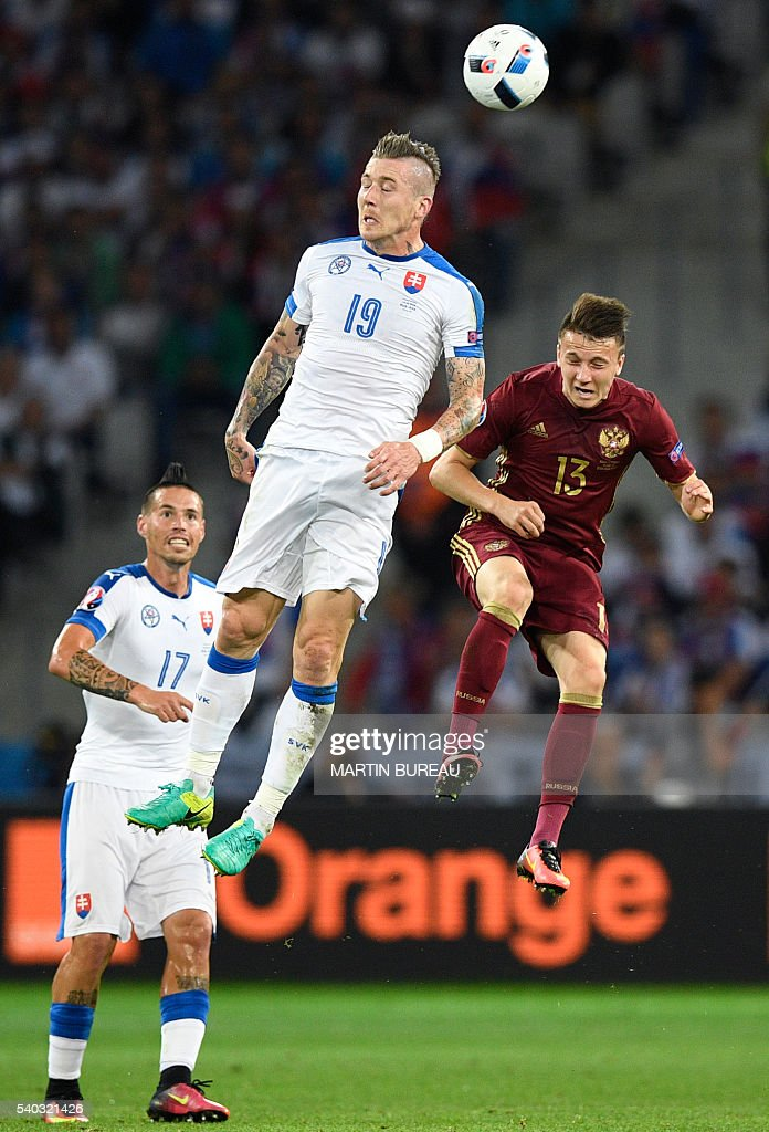 Slovakia's midfielder Juraj Kucka (C) jumps for the ball with Russia's midfielder Aleksandr Golovin (R) beside Slovakia's midfielder Marek Hamsik during the Euro 2016 group B football match between Russia and Slovakia at the Pierre-Mauroy stadium in Villeneuve-d'Ascq, near Lille on June 15, 2016. / AFP / MARTIN