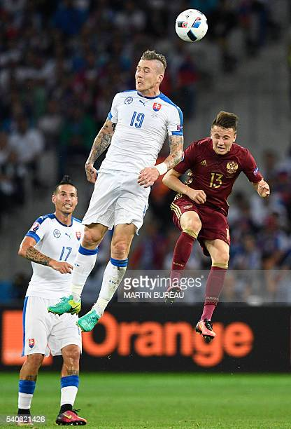 Slovakia's midfielder Juraj Kucka jumps for the ball with Russia's midfielder Aleksandr Golovin beside Slovakia's midfielder Marek Hamsik during the...