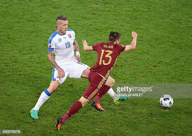 Slovakia's midfielder Juraj Kucka tackles Russia's midfielder Aleksandr Golovin during the Euro 2016 group B football match between Russia and...