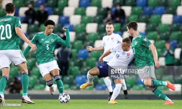 Slovakia's midfielder Stanislav Lobotka vies for the ball against Northern Ireland's defender Jamal Lewis and Northern Ireland's midfielder Paddy...