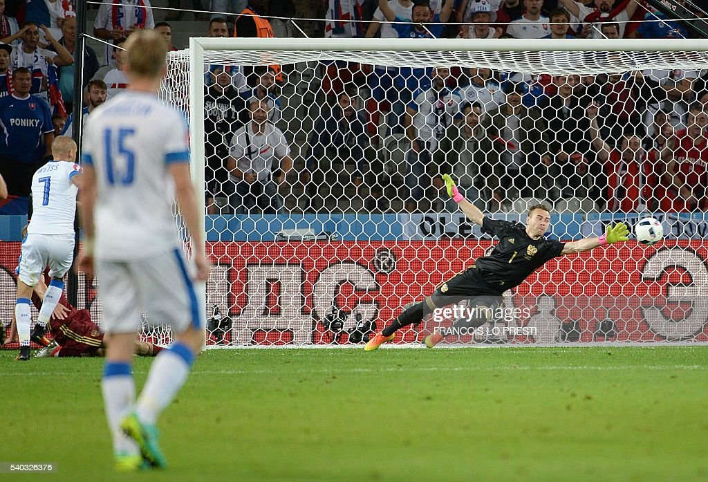Slovakia's midfielder Vladimir Weiss (L) shoots to score past Russia's goalkeeper Igor Akinfeev (R) during the Euro 2016 group B football match between Russia and Slovakia at the Pierre-Mauroy Stadium in Villeneuve-d'Ascq, near Lille, on June 15, 2016. / AFP / FRANCOIS