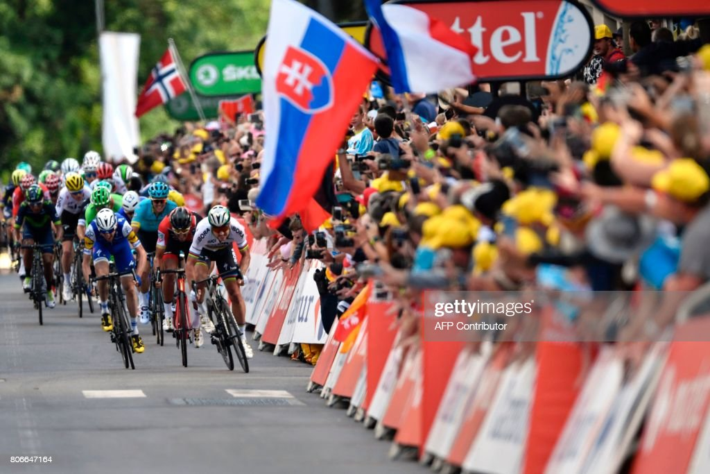TOPSHOT - Slovakia's Peter Sagan (R) sprints towards the finish line, past a flag of Slovakia, at the end of the 212,5 km third stage of the 104th edition of the Tour de France cycling race on July 3, 2017 between Verviers, Belgium and Longwy, France. / AFP PHOTO / Jeff PACHOUD