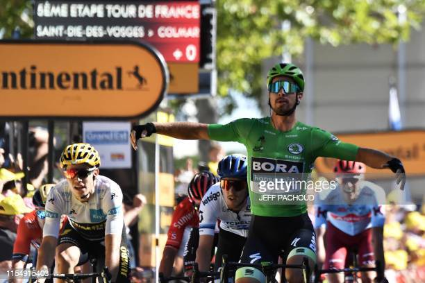 TOPSHOT Slovakia's Peter Sagan wearing the best sprinter's green jersey celebrates past Belgium's Wout van Aert wearing the best young's white jersey...