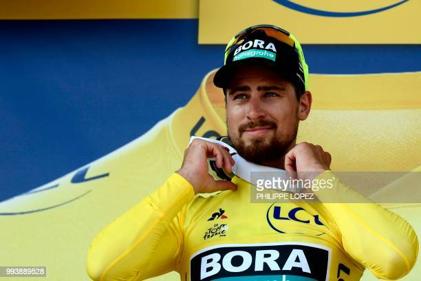 Slovakia's Peter Sagan wearing the overall leader's yellow jersey reacts on the podium after the second stage of the 105th edition of the Tour de...