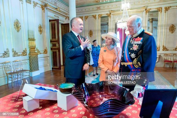 Slovakia's President Andrej Kiska Queen Sonja of Norway and King Harald of Norway look at gifts from Kiska at the Royal Palace in Oslo Norway June 4...