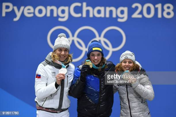Slovakia's silver medallist Anastasiya Kuzmina Sweden's gold medallist Hanna Oeberg and Germany's bronze medallist Laura Dahlmeier pose on the podium...