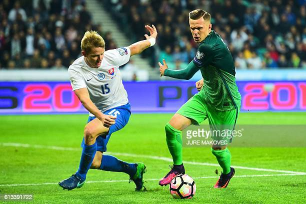 Slovakia's Tomas Hubocan vies for the ball with Slovenia's Josip Ilicic during the FIFA World Cup qualifying football match between Slovenia and...