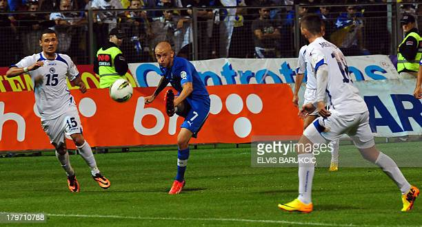 Slovakia's Vladimir Weiss shoots for goal while Bosnia and Herzegovina's Sejad Salihovic and Haris Medunjanin atempt to block ball during a WC2014...