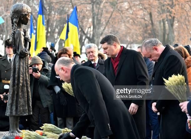 SlovakPresidentAndrej Kiska and Latvia's President Raimonds Vejonis place symbolic sheaves of wheat during a commemoration ceremony at a monument...