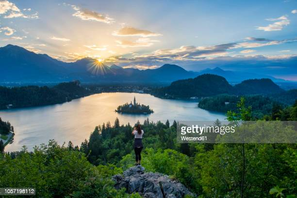 slovenia, bled,  young woman taking picture of bled island and church of the assumption of maria at sunrise - 雰囲気 ストックフォトと画像