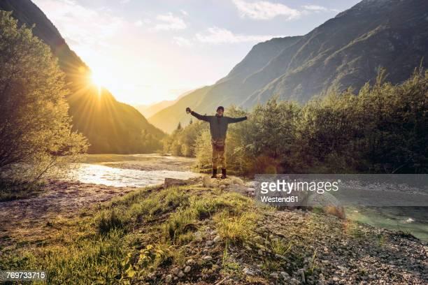 slovenia, bovec, man standing at soca river - les bras écartés photos et images de collection