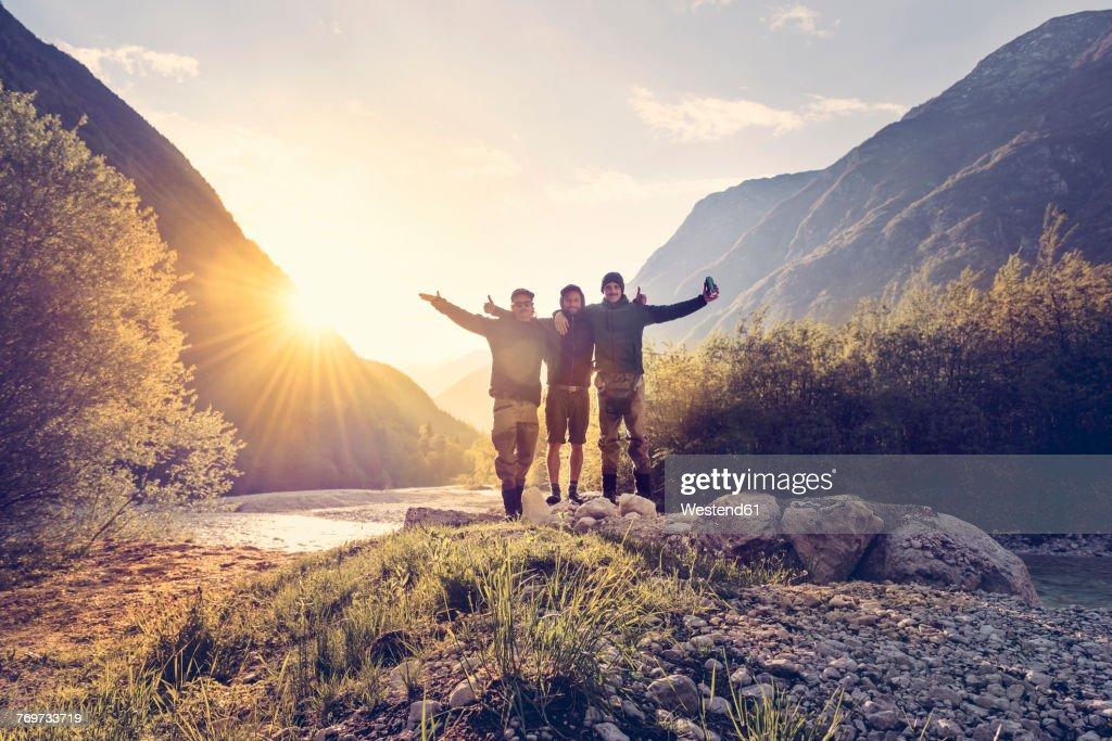 Slovenia, Bovec, three friends at Soca river at sunset : Stock Photo
