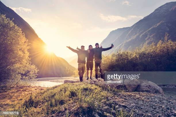 slovenia, bovec, three friends at soca river at sunset - freizeitaktivität stock-fotos und bilder