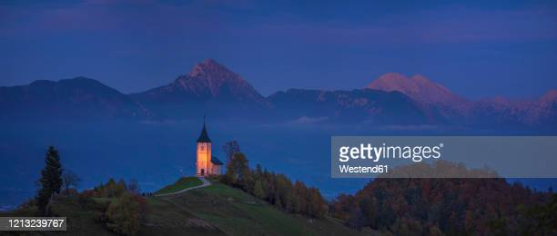 slovenia, church of st primoz near jamnik at dusk - kranj stock pictures, royalty-free photos & images