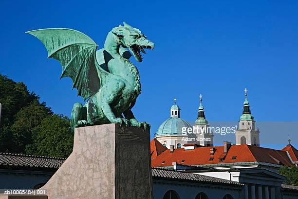 Slovenia, Ljubljana, dragon statue constructed of sheet copper on Dragon Bridge and Church of St. Nicholas