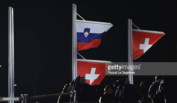 Slovenian and a Swiss flag are raised on the same flagpole for joint gold medalists Tina Maze of Slovenia and Dominique Gisin of Switzerland and...