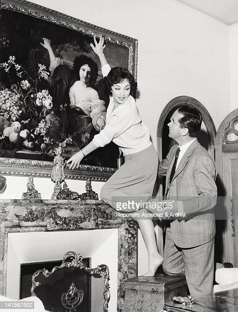 Slovenian doctor Milko Skofic holding the Italian actress Gina Lollobrigida his wife standing on a stool in their residence on the Appian Way Rome...