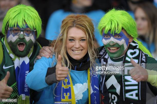 Slovenian fans with painted faces pose for a photograph as they await kick off in the World Cup 2018 qualification football match between Scotland...
