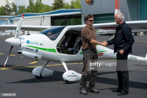Slovenian pilot biologist photographer and adventurer Matevz Lenarcic is greeted by Ivo Boscarol a Slovenian ultralight aircraft maker after...