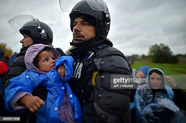 Slovenian police help migrants at the Trnovec border crossing after being stuck in cold and wet weather on October 19 2015 in Trnovec Croatia...